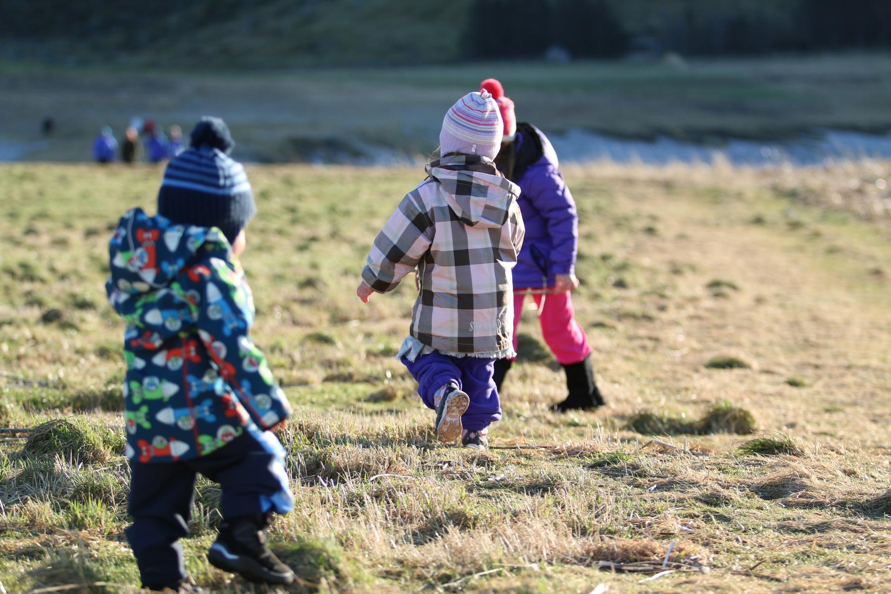 Barn som spring på slette. Haust. Foto.