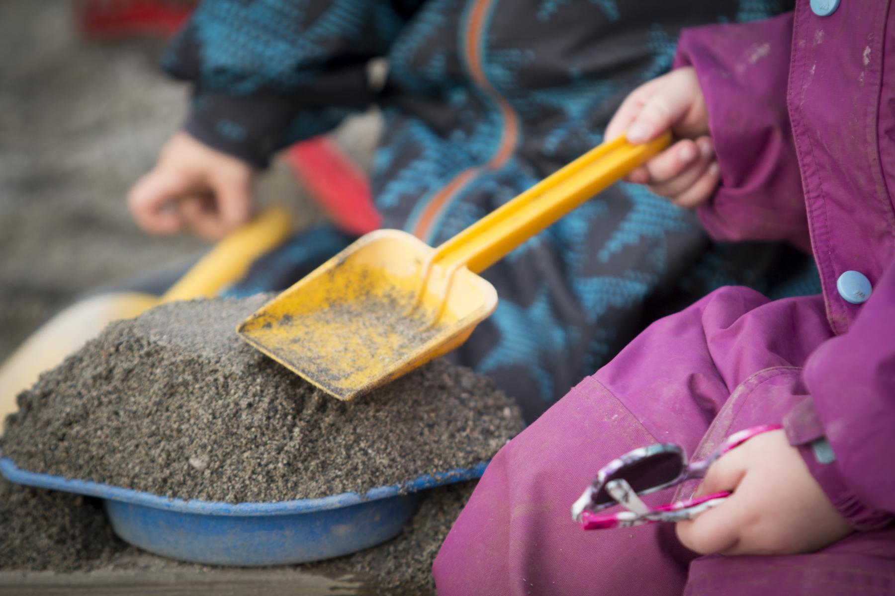 Barn som leiker med spade i sandkasse. Bilete.