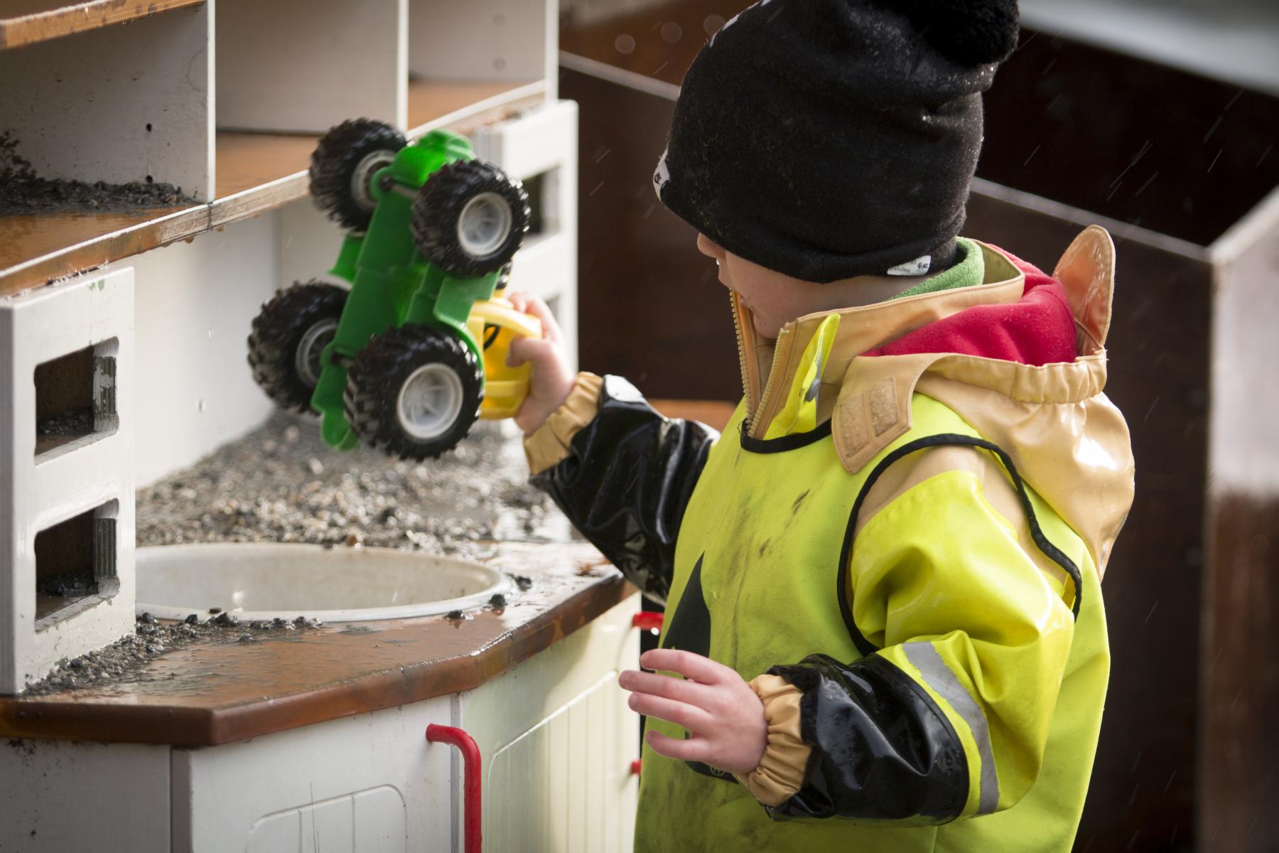 Barn som leikar med traktor i barnehage. Foto.