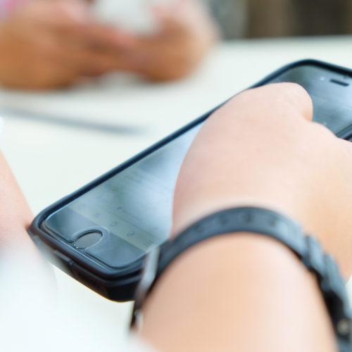 Hand som holder mobiltelefon. Foto.