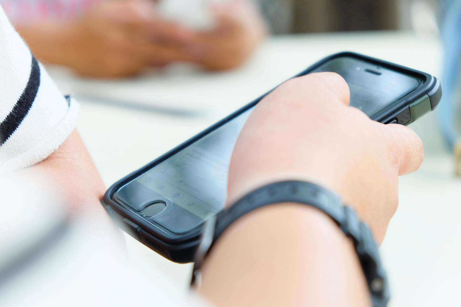 Hand som holder mobiltelefon