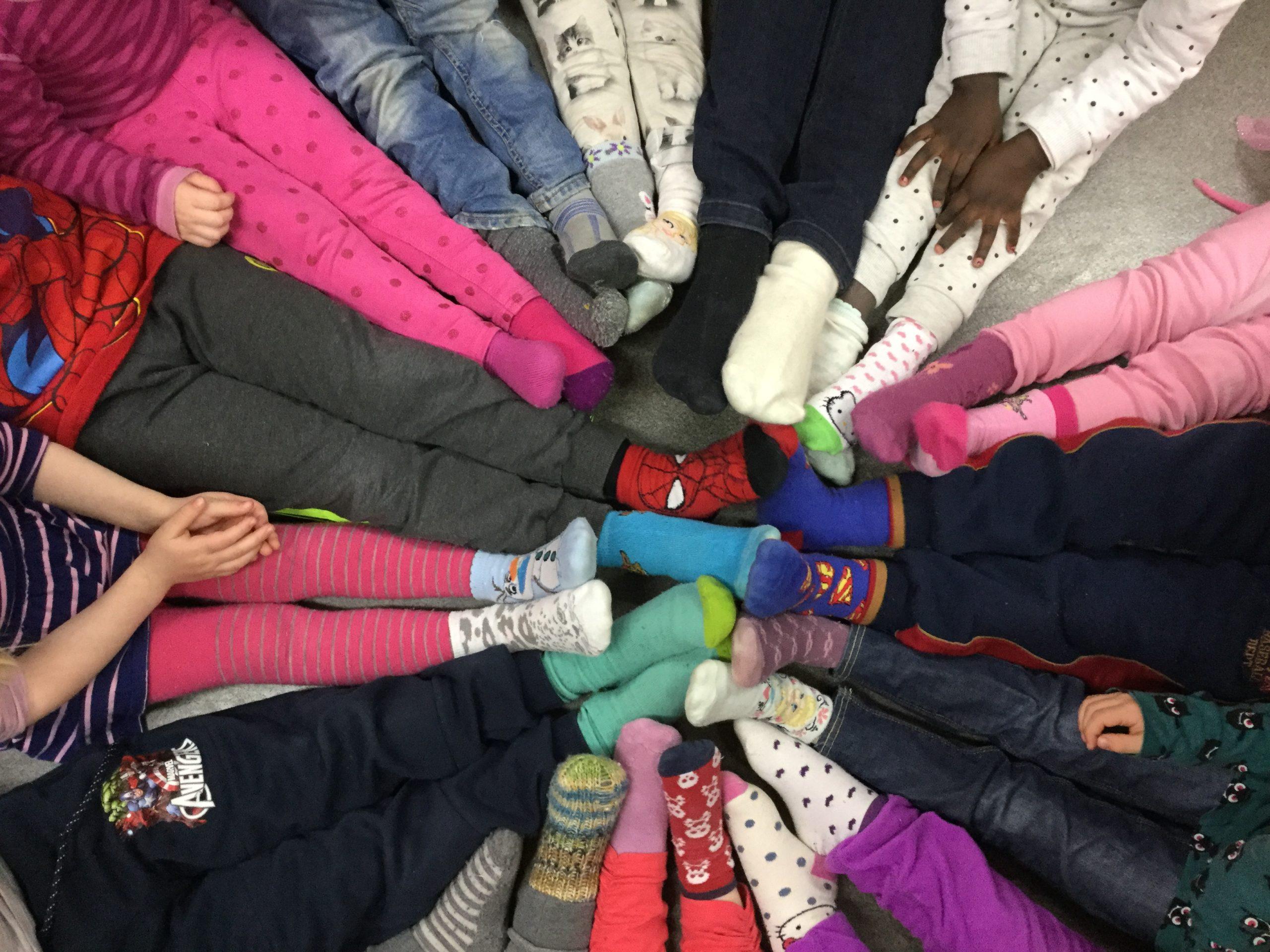 Mange born i ring med beina inn mot midten og mange ulike sokkar. Foto.