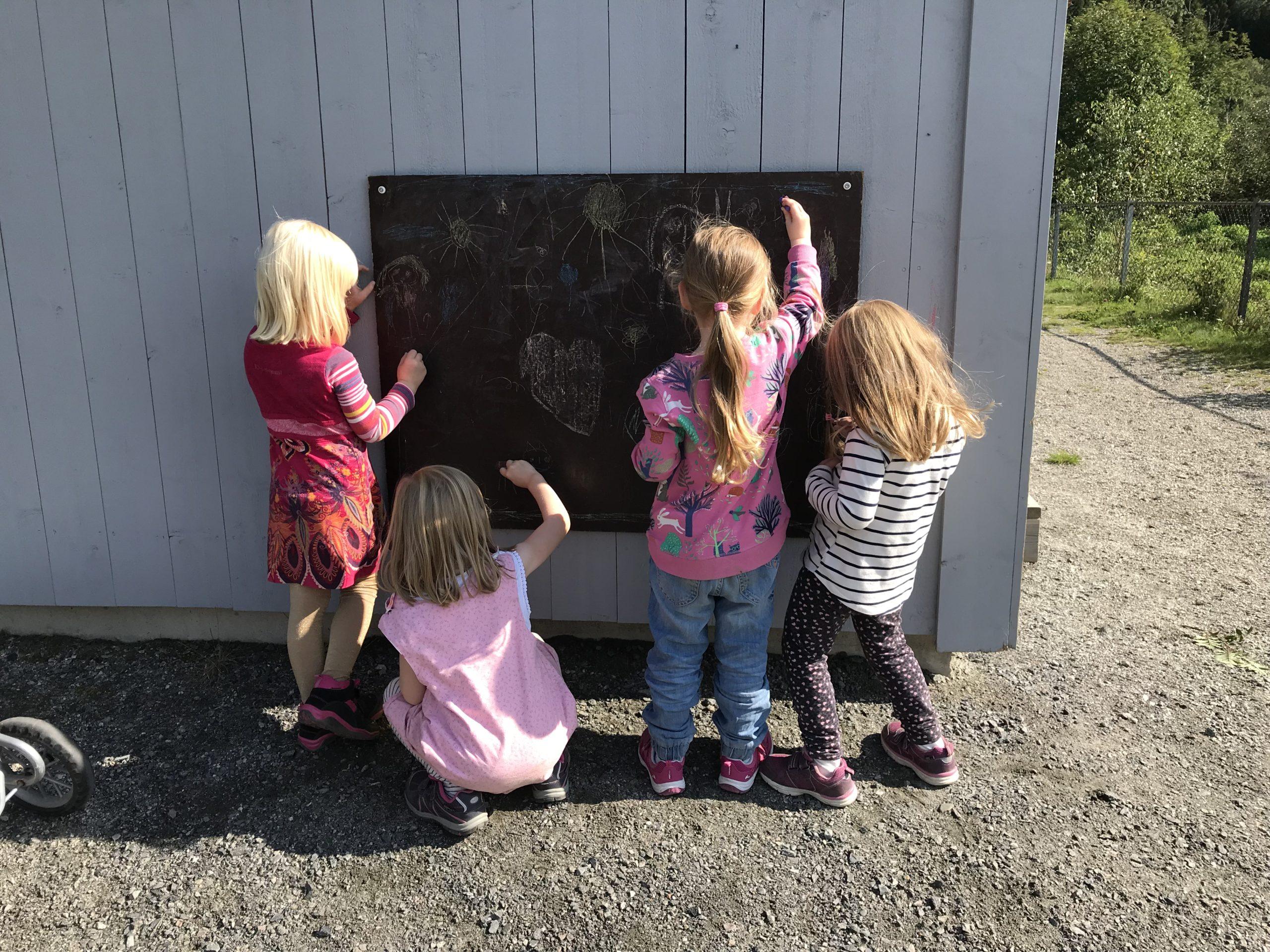 Fire born som skriv på tavle ute i barnehage. Foto.