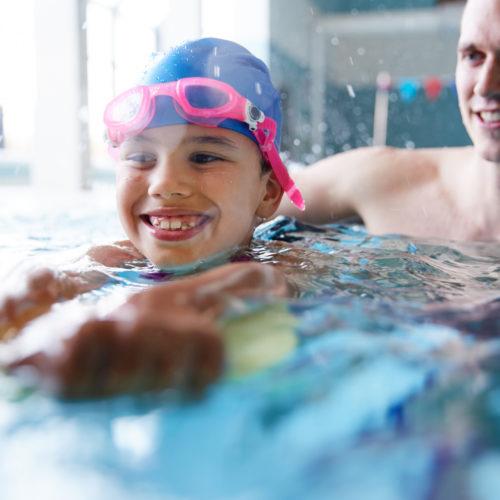 Jente i badebasseng som får symjeopplæring av vaksen. Foto.