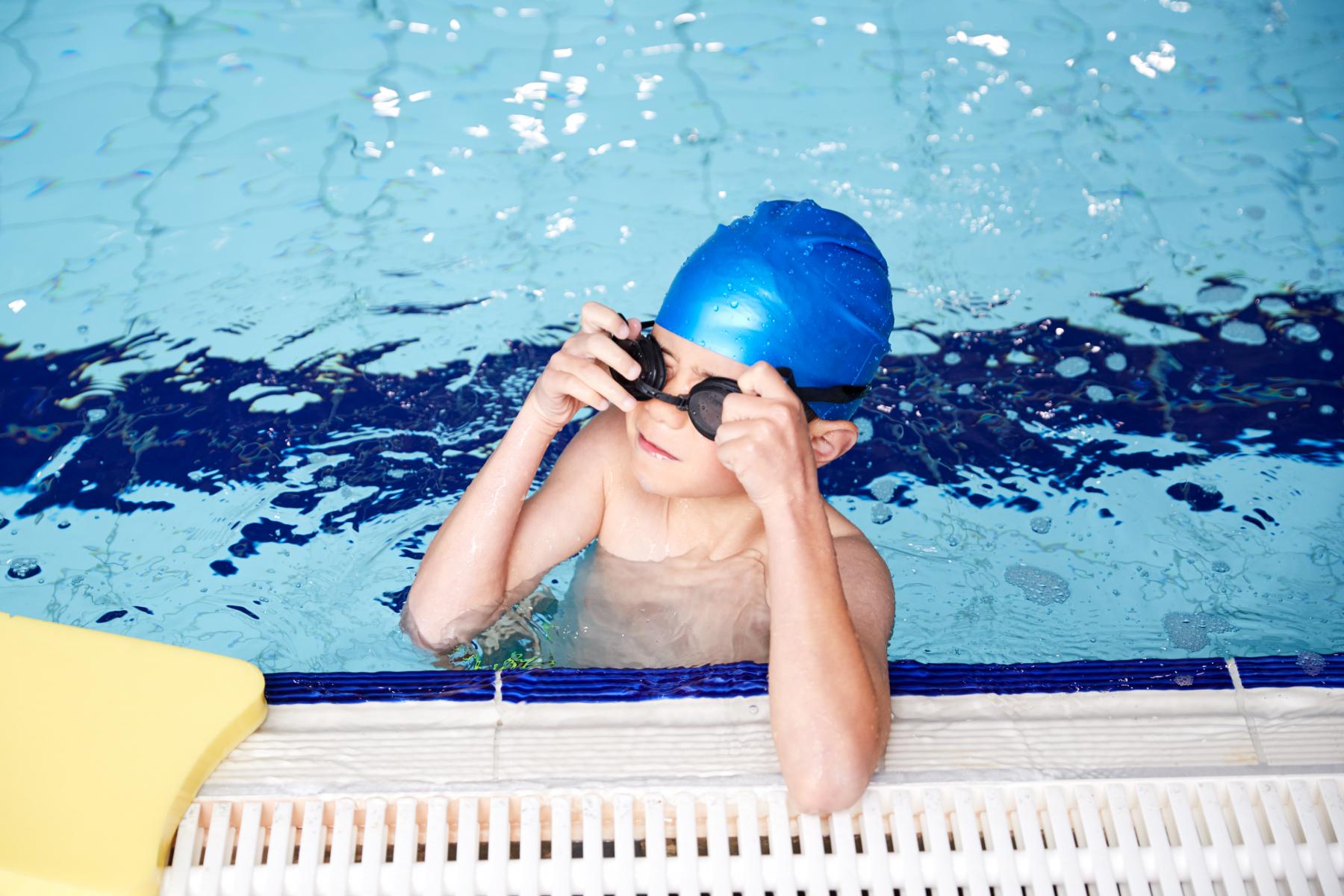 Gut i badebasseng med symjebriller.