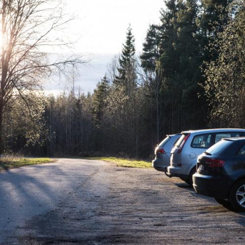 Tre parkerte biler på ein landleg parkeringsplass. Foto.