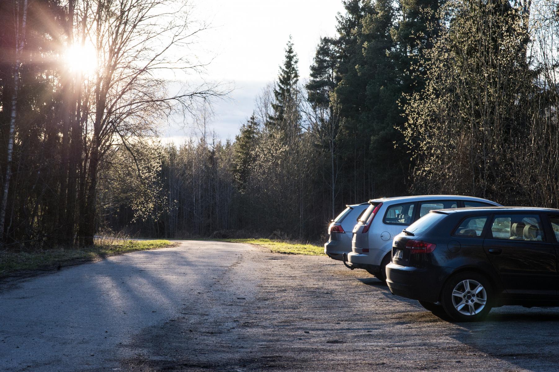 Tre parkerte biler på ein landleg parkeringsplass