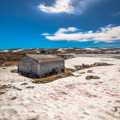 Gamalt naust i Hardangervidda nasjonalpark med snø, vatn og fjell. Foto.