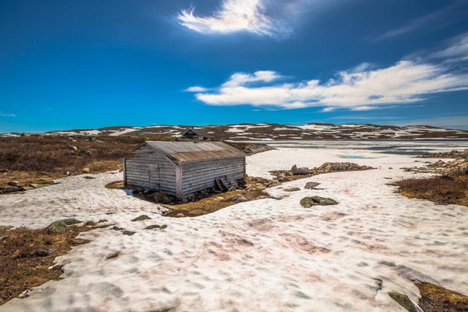 Gamalt naust i Hardangervidda nasjonalpark med snø, vatn og fjell