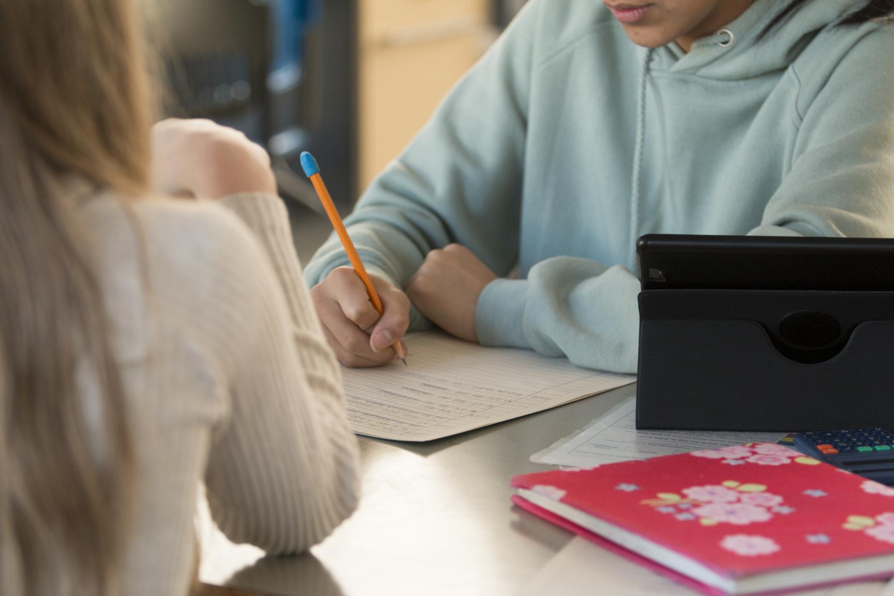 Elever som sitter med pult og arbeider.