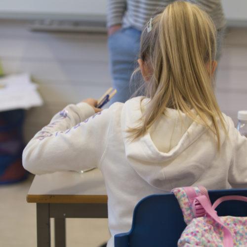 Elev på småskulen som sitter ved pult og jobber. Foto.