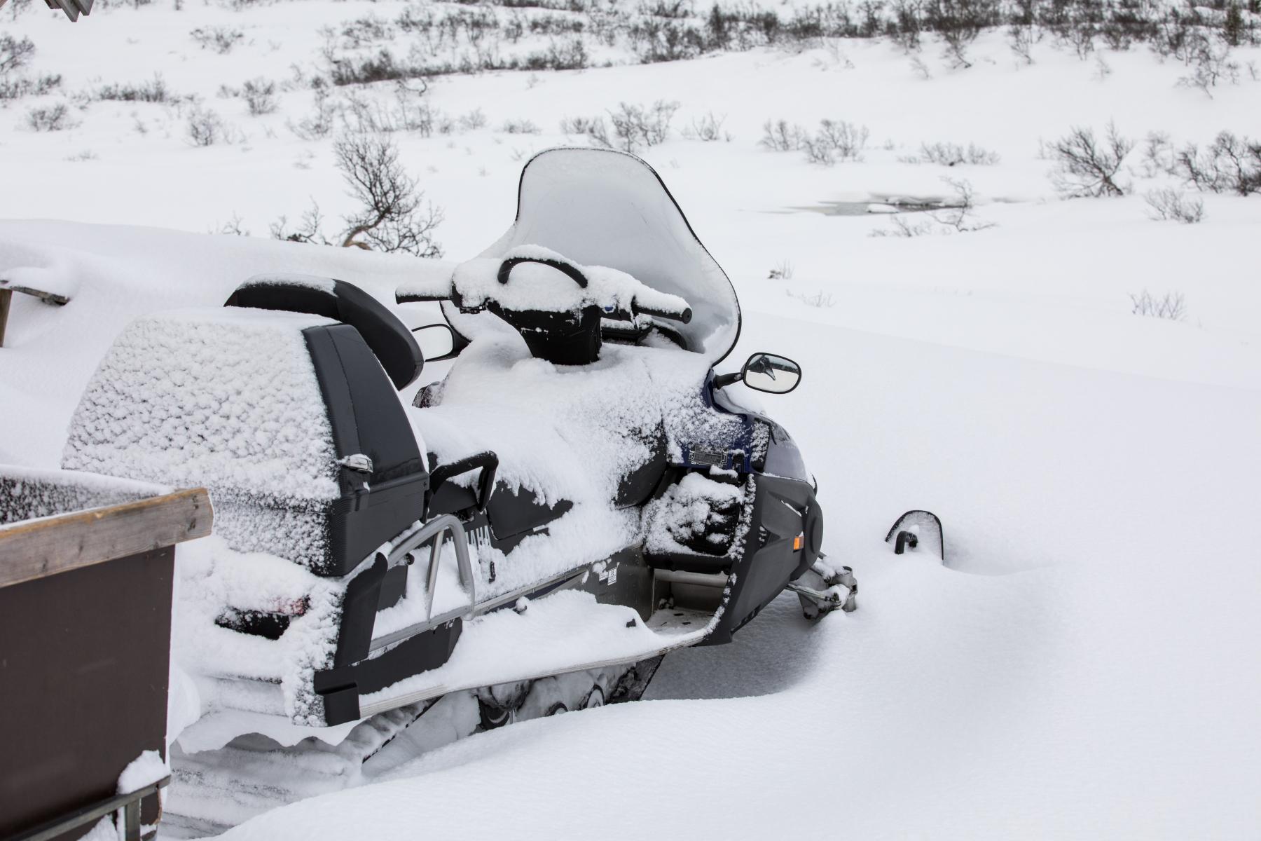 Skuter som står parkert dekt med eit lite snølag over seg. Foto.