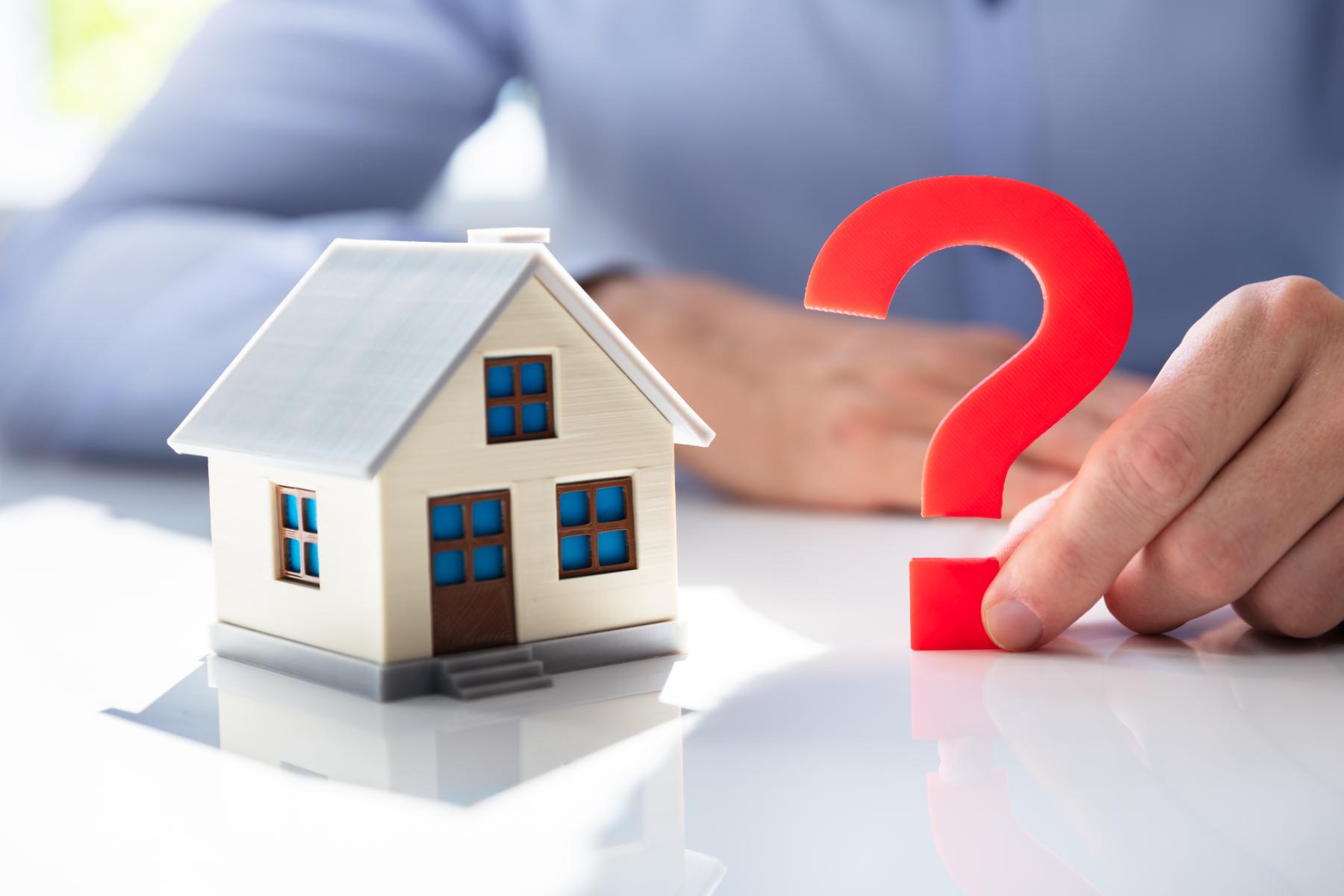 Spørsmålsteikn ståande ved siden av lite modell hus