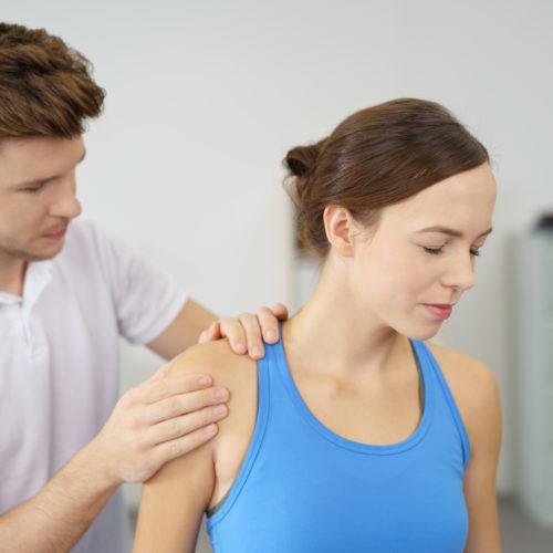 Dame som får hjelp med vond skulder av mannleg fysioterapeut. Foto.