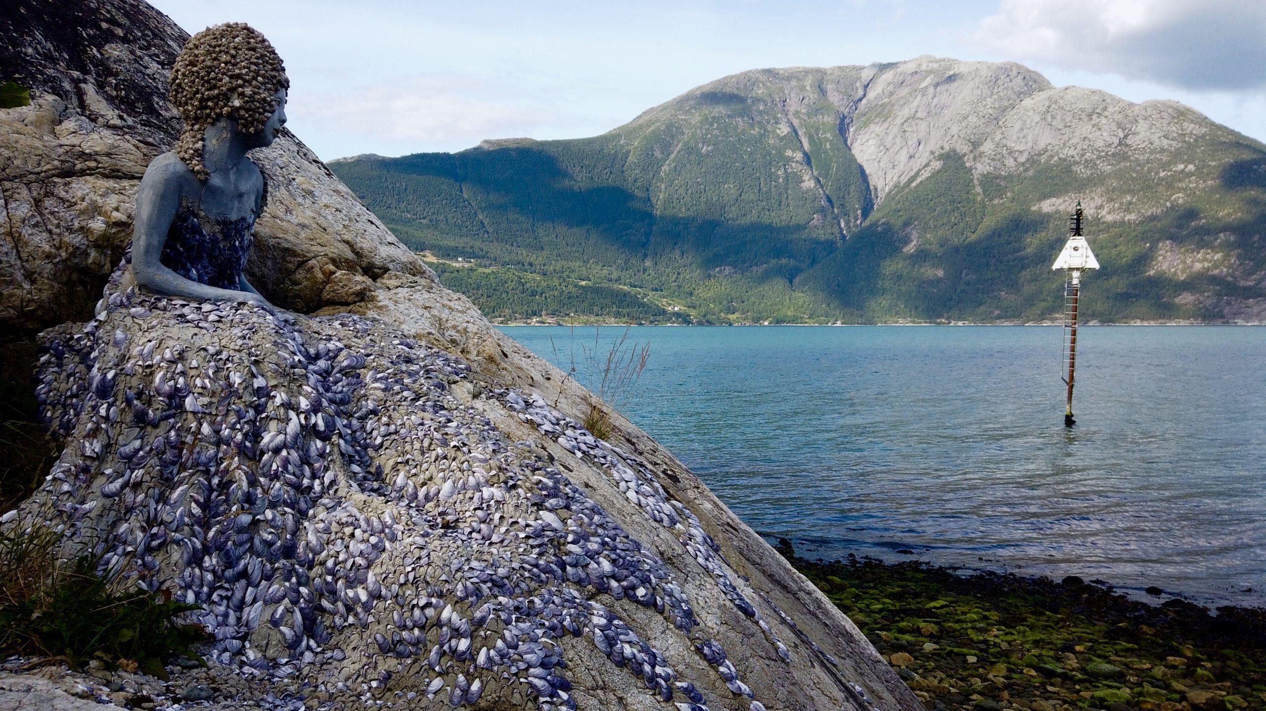 Bilete av havfrue i stein på Utne som skuer utover fjorden. Foto.
