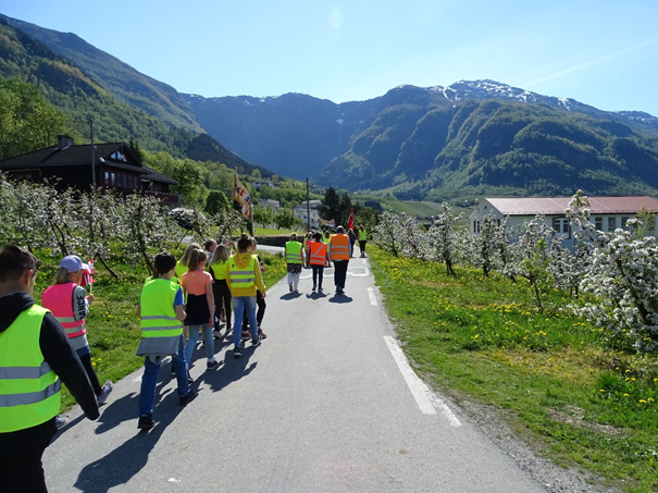 Elever som går på tur blant epletre i bløming