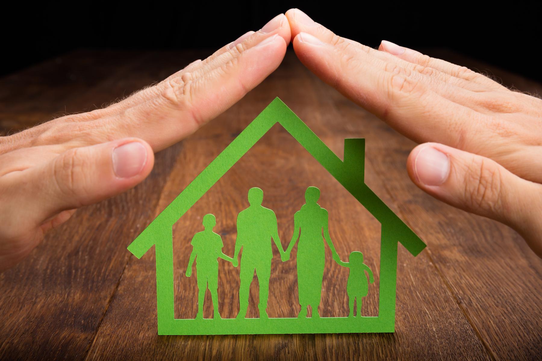 1Grønt ikon av familie inne i eit hus beskytta av to hender