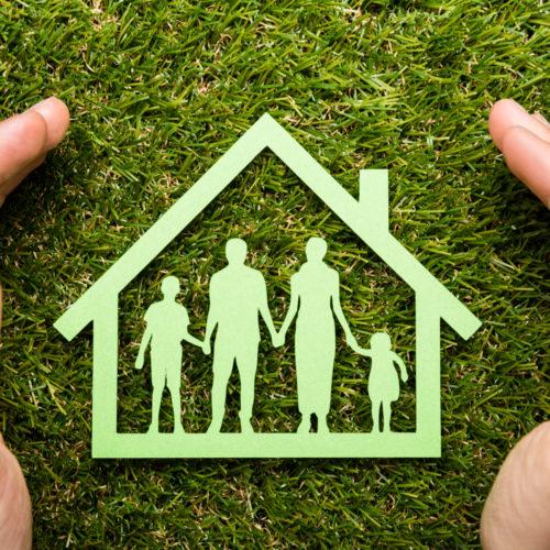 Grønt ikon av familie inne i eit hus beskytta av to hender. Foto.