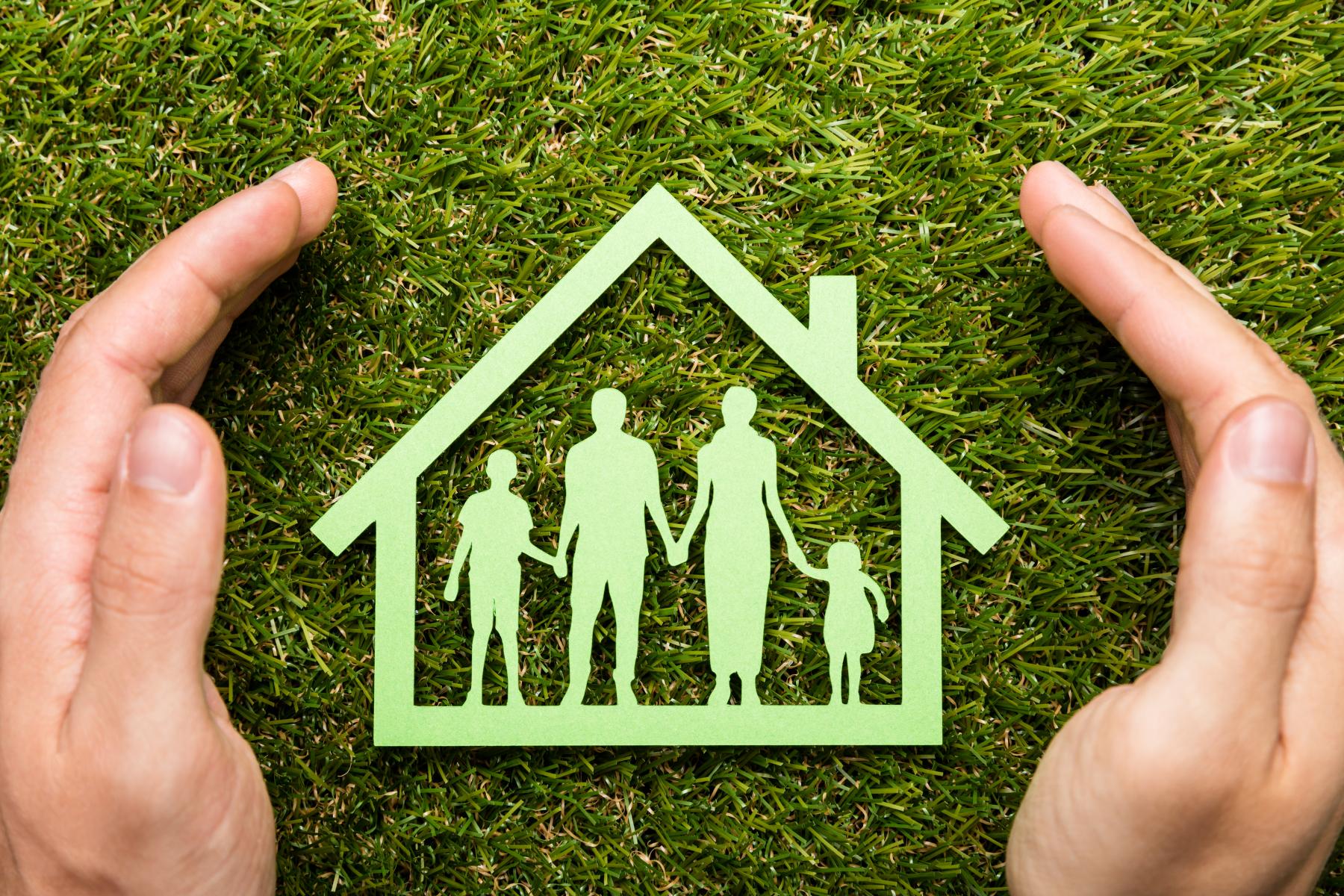 Grønt ikon av familie inne i eit hus beskytta av to hender