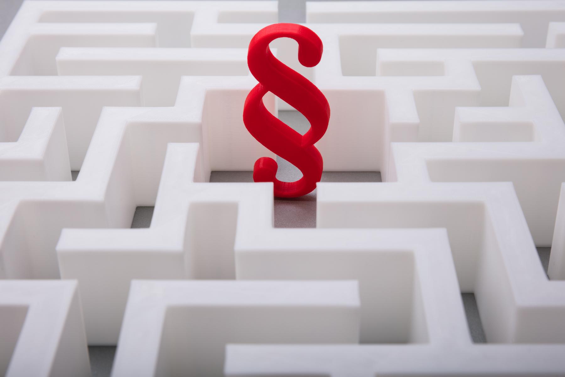 Raud paragraf symbol i midten av ein labyrint