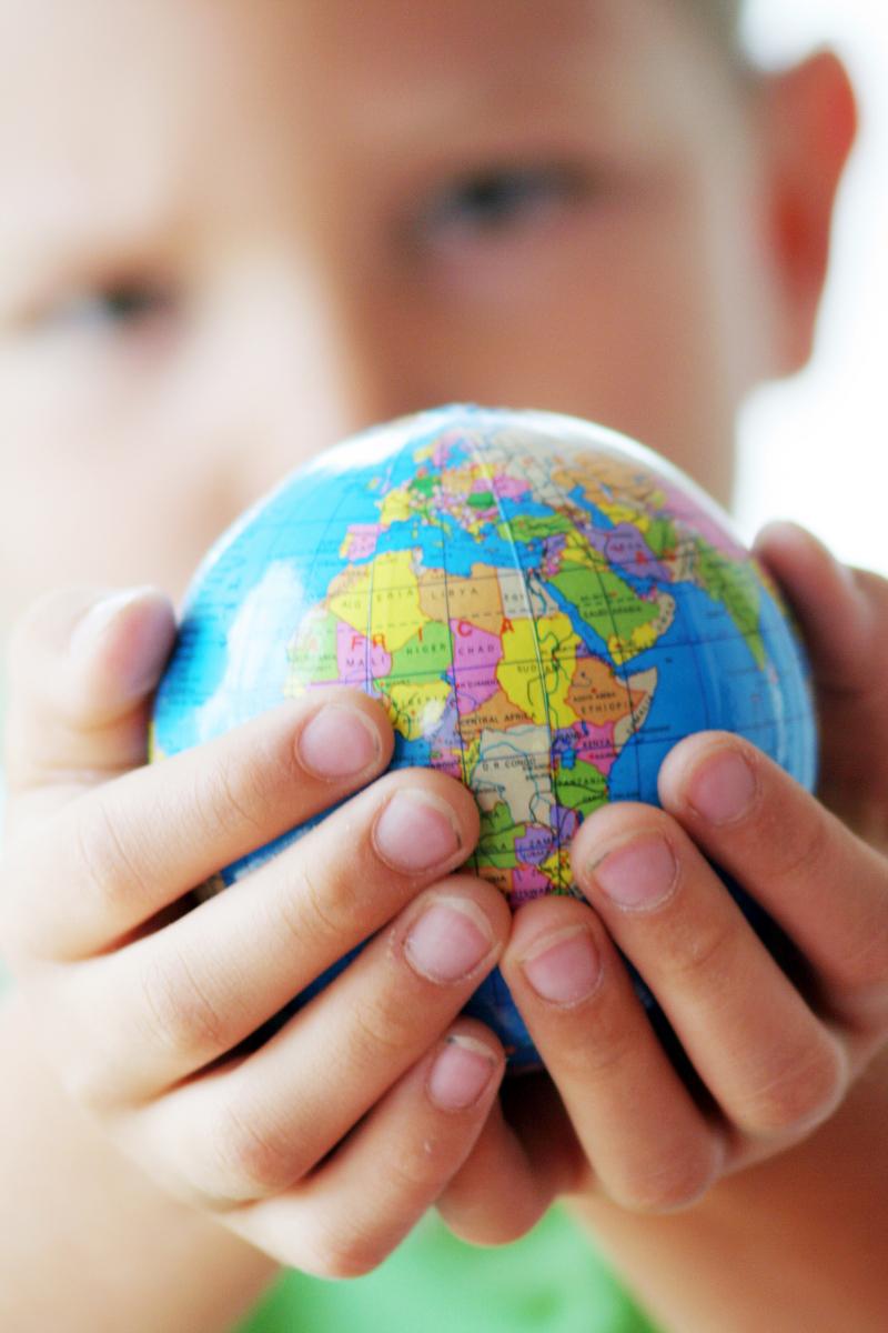 Gutt som holder jordkloden i hendene sine