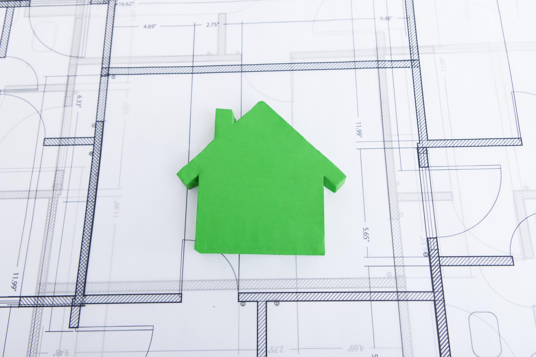 Grønt modellhus oppå planteikning