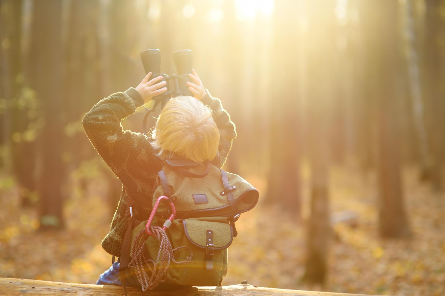 Liten gut som er på tur i skogen og kikke på omgivnadane med kikkert. Foto.