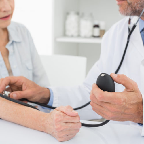 Lege som måler blodtrykk på eldre dame. Foto.