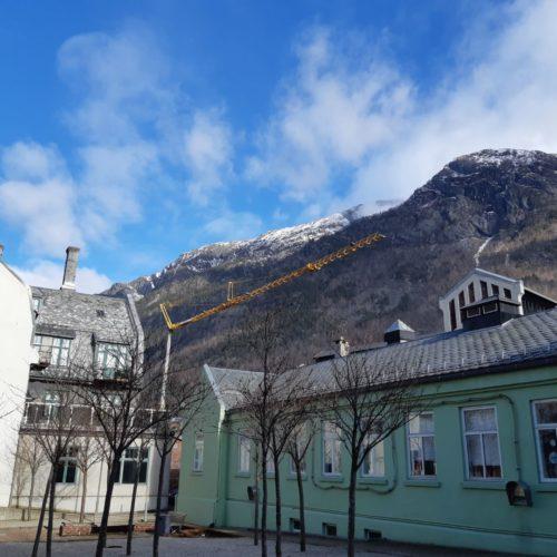 Heisekran over bebyggelsen i Odda med fjell i bakgrunnen. Foto.